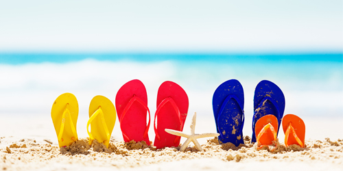 Let the family vacation fun begin! Red, blue, yellow, and orange flipflop rubber sandals sit on a sandy beach with calm sea in the background. Plenty of copy space on the sand and sea.